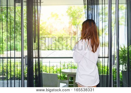 Young woman woke up and drinking coffee while looking through the window under sunlight. Good morning.