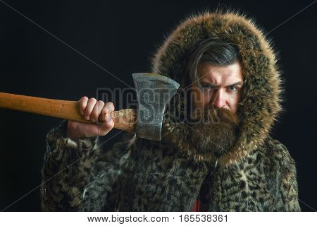 handsome bearded man or woodman guy with fashionable mustache and beard on serious face in brown fur coat holds sharp axe or ax on black background copy space