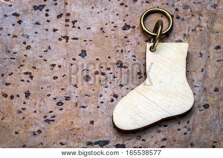 wooden sock keychain on brown cork background