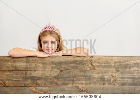 Charming princess is peeping over wooden fence with interest. She is smiling. Isolated on background