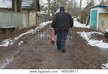 Elderly peasant with walking stick goes on an empty street of rural village Pidstavky Sumskaya oblast Ukraine