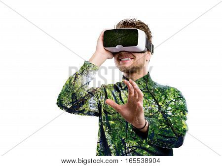 Double exposure. Hipster man in denim shirt wearing virtual reality goggles. Green trees. Isolated.