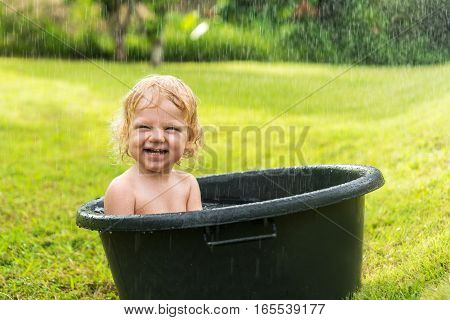 Happy blonde baby boy sitting in a basin with water when it rains. Baby on green grass in the water tank bathing.
