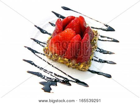 Shortbread cake with nuts decorated with strawberries and chocolate isolated on white