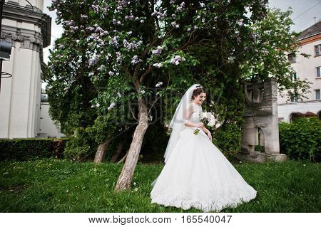 Cute Brunette Bride Under Lilac Tree With Wedding Bouquet At Hands.