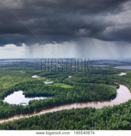 Aerial view of forest river which is on woodland in the rainy summer day during a flight.