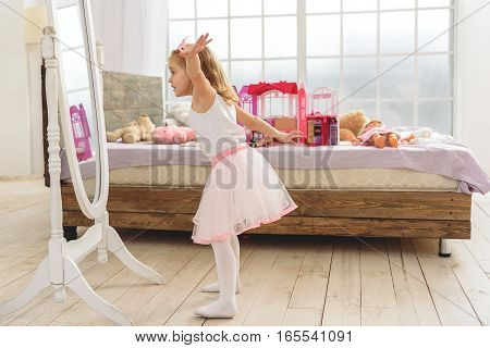 I am princess. Beautiful little girl is looking at mirror with excitement. She is standing and waving her arms. Bed with toys on background