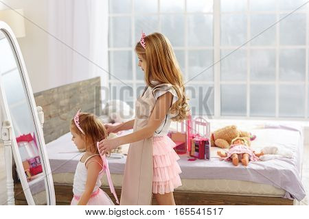 You are my little fairy. Friendly girl is wearing pink fairy wings on her smaller sister. Happy child is looking at mirror and smiling. They are standing in bedroom
