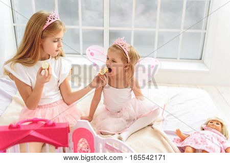 That is food for real princesses. Lovely two sisters are eating cakes with appetite. They are sitting on bed near toys