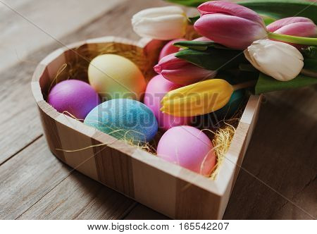 Heart shaped wooden bowl colored eggs and tulips - happy Easter