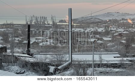 The rising sun in the city and snow over the factory