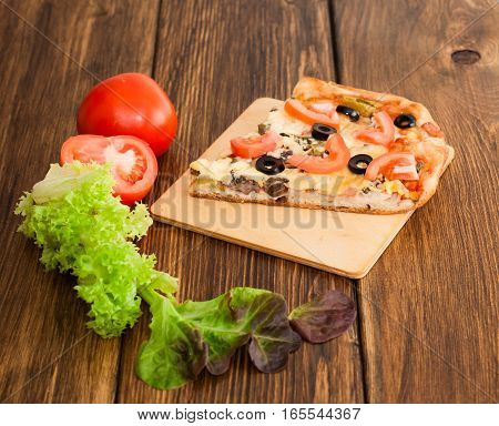 Pizza with mushrooms, ham and vegetables on a plate on a wooden background.