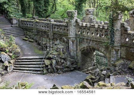 Steps leading to an ancient abandoned fortified entrance with iron gate