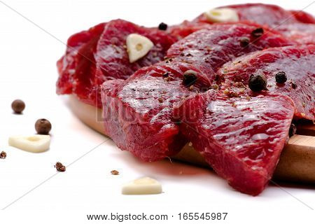 Pieces of meat with garlic isolated on white background. Raw beef. Meat. Top view.