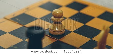 Vintage wooden chess on the chess board closeup