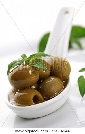 Olives on ceramic spoon with basil and olive oil