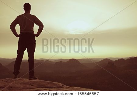 A man has his hands on hips. Sportsman silhouette in nature within daybreak