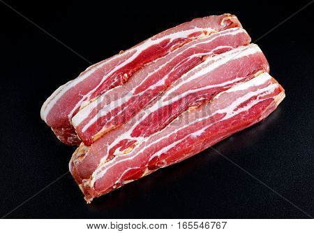 Raw smoked streaky sliced bacon on black board background.