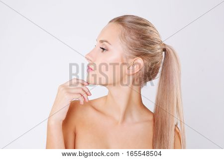 Portrait of young beautiful caucasian woman touching her face isolated over grey background. Cleaning face, perfect skin. SPA therapy, skincare, cosmetology and plastic surgery concept. Studio