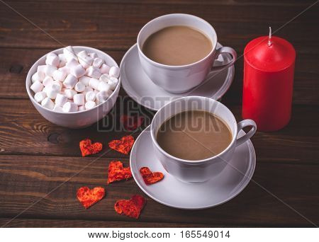 Two cups of hot cocoa or coffee with milk, marshmallows in plate, red candle and little red hearts on dark rustic wooden table. Valentines day concept