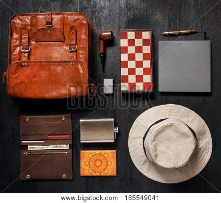 Traveler set ready for vacation. Leather bag, flask for brandy, lighter, sun glasses, paper notebook, pen, chess board, hat and smoking pipe.