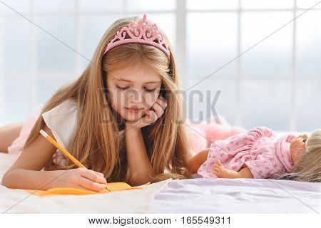 Dreamful girl is drawing on paper. She is lying on bed near doll in princess crown