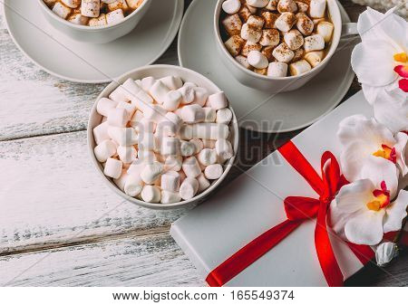 Cups with hot coffee or cocoa and marshmallows, gift box with red ribbon and flowers on white wood table. Top view. Valentines day concept. Cozy winter. Toned image.