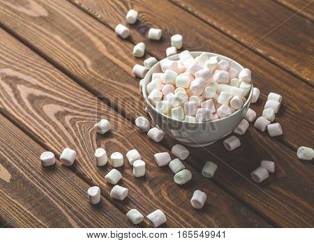 Marshmallows in plate on dark rustic wooden table background. Toned image with copy space for text
