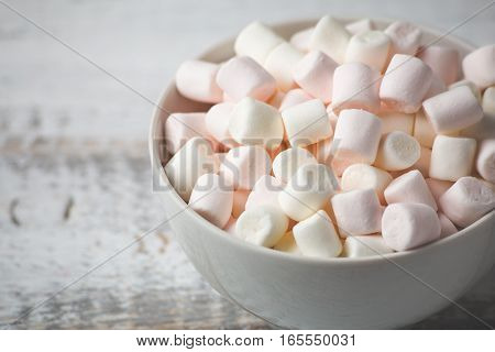 Close up image of Marshmallows in plate on white rustic wooden background. Toned image with copy space for text