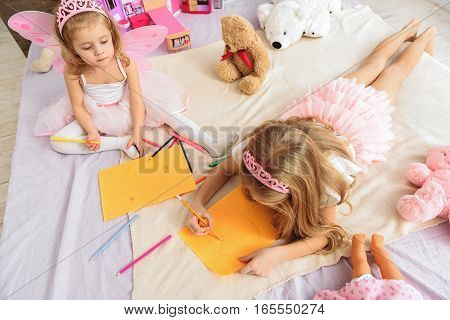 What are you drawing. Top view of two cute little sisters painting pictures. Child interested what illustration her sister creating