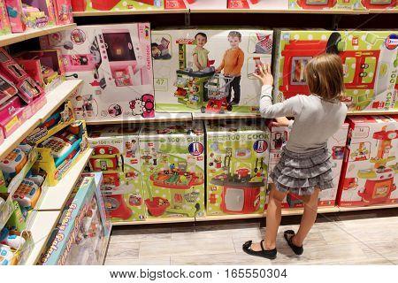 Chernihiv / Ukraine - 04 September 2015: little girl chooses a doll in a toy shop. 04 September 2015 in Chernihiv / Ukraine.