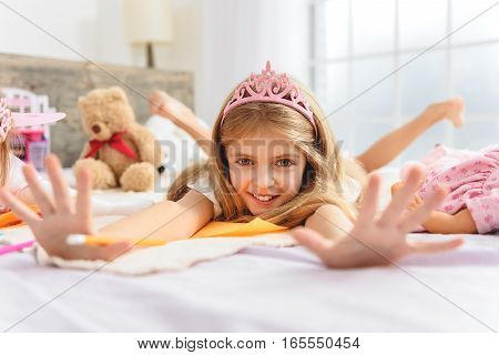 Cheerful girl with outstretched arms lying on her bed. Focus on happy face of little princess