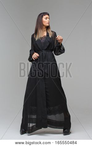 Woman which is thoughtfully in a light long black dress. Woman in sexy transparent gown, underwear and shoes hides behind her hands, covered