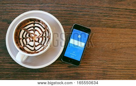 SONGKHLA THAILAND - Sep 282016: Apple iPhone with Facebook application on the screen. Facebook is a photo-sharing app for smartphones and mocha coffee on the table