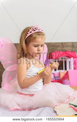 Nice pensive kid focusing her attention on closing the highlighter. She is ready to draw a picture. Sad girl is sitting in bedroom near her toys