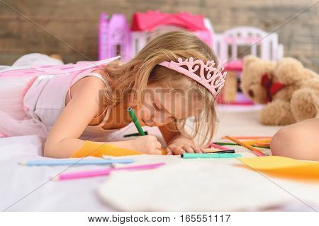 Small kid is trying to paint image with concentration. She is lying on bed. Many colored highlighters are around the girl
