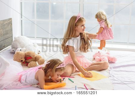 Future artists. Good-looking girls drawing different pictures. Elder sister is painting her doll and smiling. Toys are on the big bed