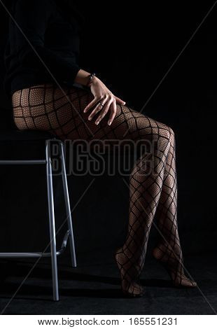 Low key photo of sexy slim beautiful legs in black net tights sitting on chair against black background