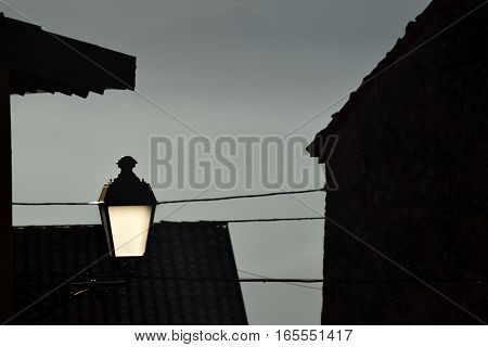 A street lamp lights in the fog