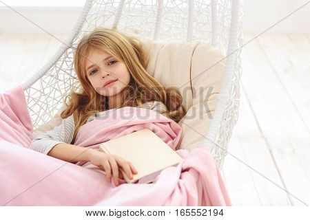 Happy little girl is holding book and dreaming. She is looking at camera and smiling. Child is lying on hammock with relaxation