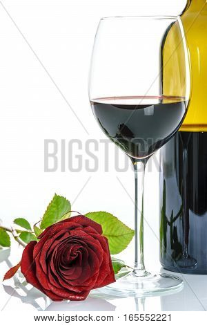 Beautiful red rose and wineglass of red wine and a bottle on a white background.
