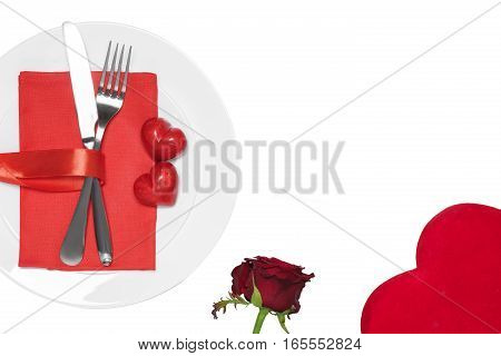 Knife, fork and hearts on the plate close-up on white background. Valentine's day concept.