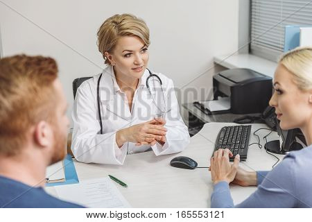 Attentive doctor with benevolent glace is listening to patients. Stethoscope on her shoulders