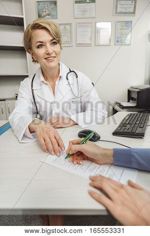 Benevolent doctor is sitting near desk. Modern stethoscope on her shoulders. She giving medical form to woman