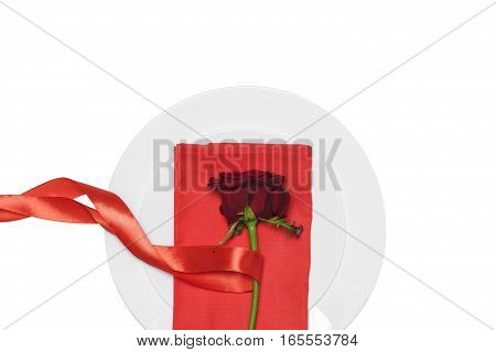 red rose with ribbon on plate on white background. Valentine's day.