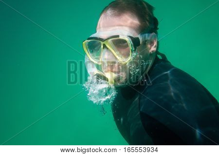 Snorkeler swimming over sea grass, green background