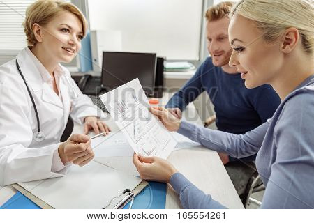 Smiling female medical advisor is sitting afore hopeful pair. Attentive woman holding sheet of paper with charts