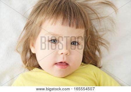 Cute Little Girl Portrait Face Lying On White Blanket