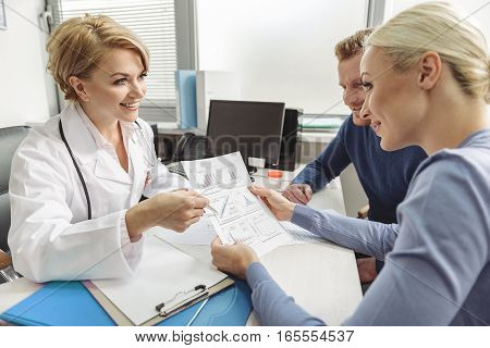Smiling doctor is sitting afore happy couple. She has good news according to paper with charts. Fortunate woman holding sheet of paper