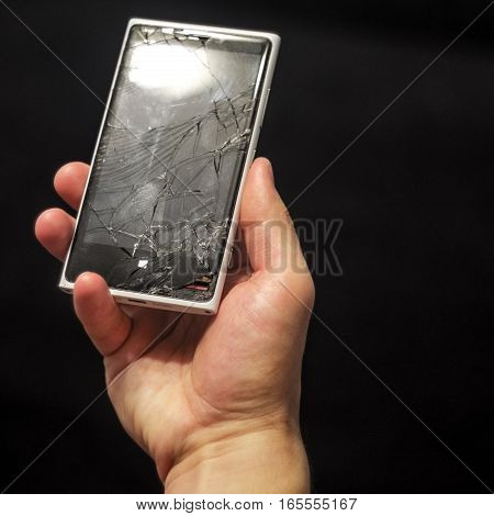Hands holding broken mobile smartphone. Broken smart phone in hand on a black background